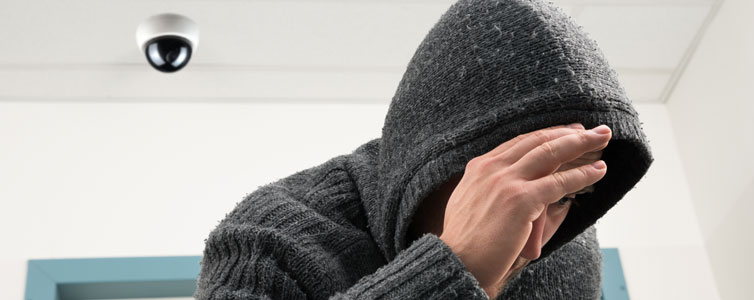 A burglar hiding from a cctv camera